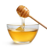 Honey in glass bowl. Honey dripping from a wooden dipper in glass bowl Royalty Free Stock Photo