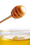 Honey in glass bowl. Honey dripping from a wooden dipper in glass bowl Royalty Free Stock Photos
