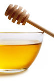 Honey in glass bowl. Glass bowl with floral honey and stick isolated on white background stock images