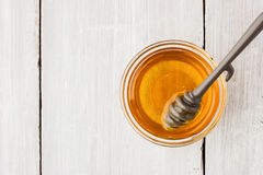 Honey in the glass bowl on the white wooden table top view Stock Photo