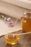 Honey in a glass bowl on a wooden boards background Royalty Free Stock Photos