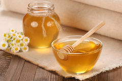 Honey in a glass bowl on a wooden boards background Stock Photos