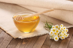 Honey in a glass bowl on a wooden boards background Stock Photo