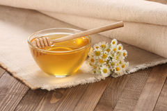 Honey in a glass bowl on a wooden boards background Stock Photography