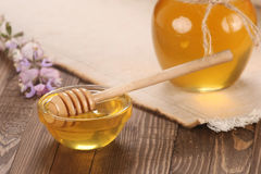 Honey in a glass bowl on a wooden boards background Royalty Free Stock Photo
