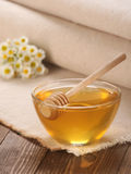 Honey in a glass bowl on a wooden boards background Stock Images
