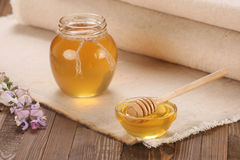 Honey in a glass bowl on a wooden boards background Royalty Free Stock Images