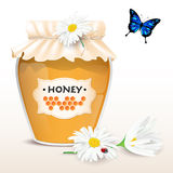 Honey in glass with flowers and butterfly Royalty Free Stock Image
