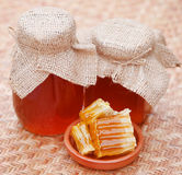 Honey in glass jar with bee hive Royalty Free Stock Photo