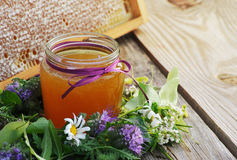 Honey in a glass jar and bee honeycombs with flowers melliferous herbs Royalty Free Stock Photo