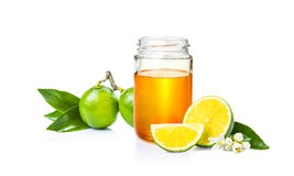 Honey in glass jar and cut lime on white bacground stock image