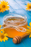 Honey in a glass jar with flowers. Honey in a jar surrounded by flowers on wooden background Royalty Free Stock Images