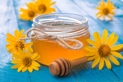 Honey in a glass jar with flowers. Honey in a jar surrounded by flowers on wooden background Stock Photo