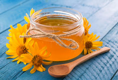 Honey in a glass jar with flowers. Honey in a jar surrounded by flowers on wooden background Royalty Free Stock Photo