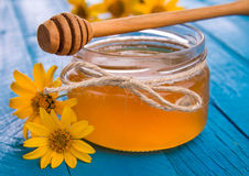 Honey in a glass jar with flowers. Honey in a jar surrounded by flowers on wooden background Stock Images
