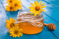 Honey in a glass jar with flowers. Honey in a jar surrounded by flowers on wooden background Royalty Free Stock Image