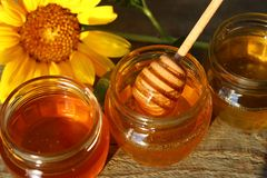 Honey in a glass jar with flowers on the wooden floor. stock photos