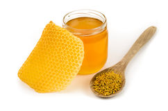 Honey. Glass jar full of honey with honeycomb and wooden spoon with pollen on white background stock image
