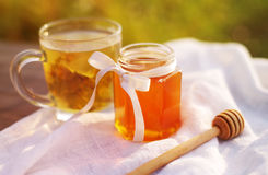 Honey in a glass jar and herbal tea. In a circle on white linen fabric. Honey and tea. Soft focus Stock Photo