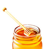 Honey in a glass jar with honey dipper  isolated on white backgr Royalty Free Stock Image