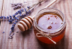 Honey in a glass jar and lavender flowers close-up. Honey in a glass jar and lavender flowers on the wooden table close-up Royalty Free Stock Image