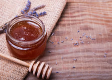 Honey in a glass jar and lavender flowers on the wooden table Royalty Free Stock Photography