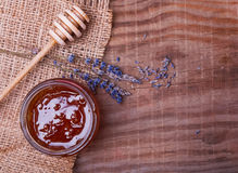 Honey in a glass jar and lavender flowers on the wooden table Stock Photography