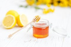 Honey in a glass jar and a lemon. Honey dipper. The concept of h. Ealthy food, vegetarianism, autumn, colds,  treatment, cure, therapy, medication Stock Photos