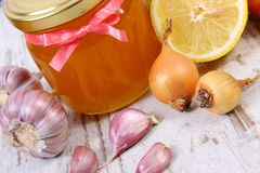Honey in glass jar, onion, lemon and garlic, healthy nutrition and strengthening immunity Stock Images