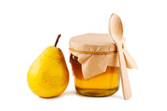 Honey in glass jar, pear, spoon. Royalty Free Stock Images