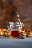 Honey in glass jar on a rustic background. Food background concept Stock Images