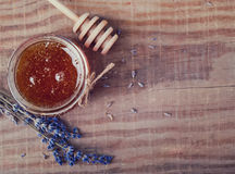 Honey in a glass jar, spoon and lavendre flowers on the wooden t Stock Photos