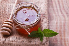 Honey in a glass jar,spoon and mint leaves on the wooden. Honey in a glass jar, honey spoon and mint leaves on the wooden table close-up Royalty Free Stock Photos