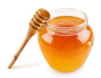 Honey in a glass jar with a stick. On a white background Royalty Free Stock Photography
