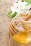 Honey in glass jar and stick. With blossom flowers Stock Photography