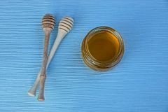 Honey in a glass jar and two tablespoons for honey on a table. Honey in a glass jar and two spoons for honey on a blue table Stock Image