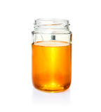 Honey in glass jar on white bacground. Honey in clear glass jar on isolated white background Stock Photography