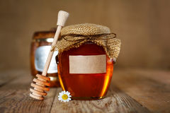 Honey in glass jar. On a wooden background Stock Photography