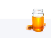 Honey in glass jar and wooden honey dipper on white and light gr royalty free stock photos