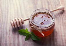 Honey in a glass jar the wooden table. Honey in a glass jar and honey spoon on the wooden table Royalty Free Stock Photography