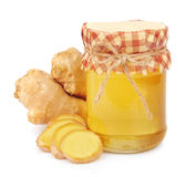 Honey in glass jars and a ginger root Stock Images