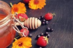 Honey glass,wooden dipper,berries, calendula Royalty Free Stock Photo