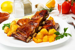 Honey glazed barbecued ribs. With baked potato stock image