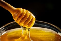 Honey with gold color flows down from a spoon. Healthy food concept. Healthy eating. Diet. Selective focus. Horizontal royalty free stock image