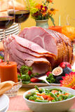 Honey ham. Holiday table setting with delicious whole baked sliced ham, fresh strawberries, figs, vegetable salad and glasses of red wine Royalty Free Stock Images
