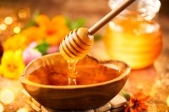 Honey. Healthy organic thick honey dripping from the honey dipper in wooden bowl. Sweet dessert Stock Photo