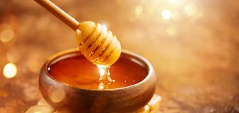 Free Honey. Healthy Organic Thick Honey Dripping From The Honey Dipper In Wooden Bowl. Sweet Dessert Stock Photo - 123515100