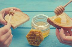 Honey and honey accessories for its use on a blue wooden background. royalty free stock photography