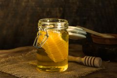 Honey with honey comb in a jar. Honey in a jar with honey comb inside Stock Photos
