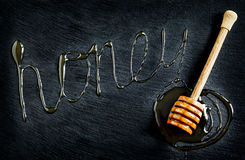 Honey and honey dipper on black background Stock Images